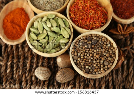 Many different spices and fragrant herbs on braided table close-up