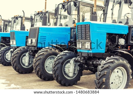 Many different tractors standing in row at agricultural fair for sale outdoors.Equipment for agriculture.Heavy industrial machines presented to an agricultural exhibition