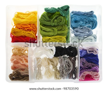 Many differently coloured embroidery threads, neatly boxed. Isolated on white background.
