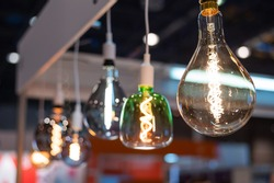Many differently shaped incandescent bulbs are suspended in the dark