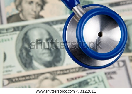 many dollar bills and stethoscope. photo icon health costs