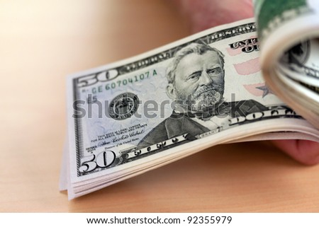 many dollar bills are counted with hands