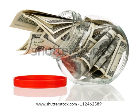 Many dollars in a glass jar isolated on white background