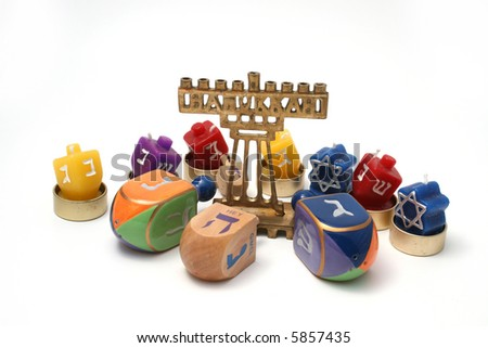 Many Dreidals (tops), candle dreidals and small hannukia (Menorah or candelabra) against a white background