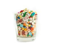 Many drug and pill fill in the glass on white background. Rational drug use and polypharmacy concept with copy space for text