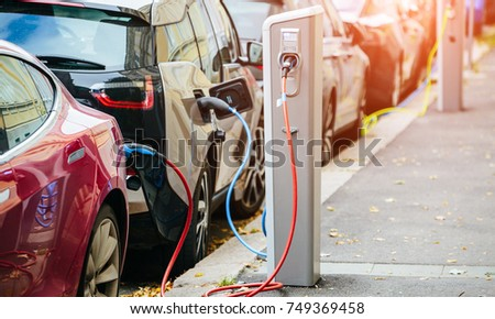 Many electric car are charged by charging stations in the parking lot