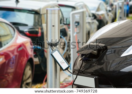 Many electric car are charged by charging stations in the parking lot #749369728