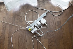 Many electrical cords connected to a single power strip or extension block. on a wooden floor near a window. A typical home scene..