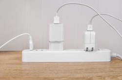 Many electrical plugs connected to a power white strip or extension block on wooden table. High-tech smart strip