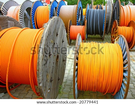 many electricity cables on wooden spools