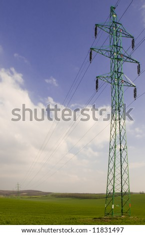 Many electricity pylons with wire in the green fields