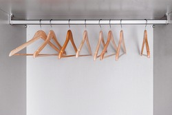 Many empty, lacquered light wood clothes hangers hang in wardrobe on metal rod. Internal space of furniture.