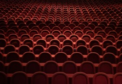 Many empty red seats in the theater.