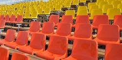 Many empty rows of orange, yellow, white plastic seats in an open stadium
