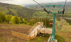 Many empty ski lift chairs in a row close up in the summer