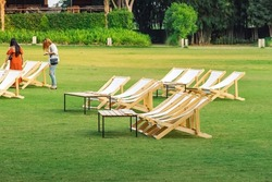 Many empty white deck chairs with tables for dinner in lawn is surrounded by shady green grass. Comfortable on outdoor patio chairs in garden.Lawn chairs in park.Sunbeds in the garden.Selective focus.
