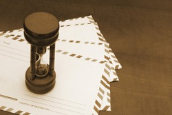 Many envelopes with hourglass on table, delivering time aconcept