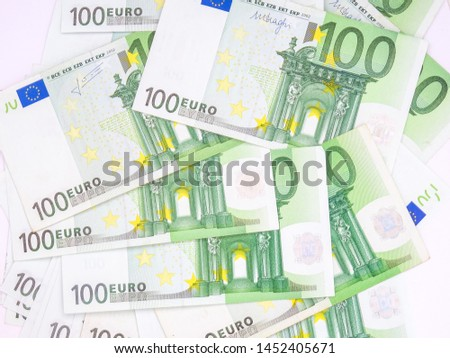Many 100 euro bills spread on white background