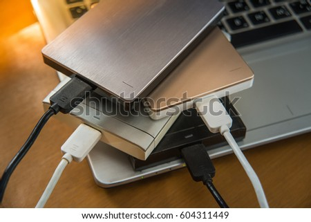 Many external hard disk on laptop  for backup files and important information using USB 3.0 connection, wooden table background. #604311449