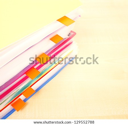 Many files and sticky notes on a desk