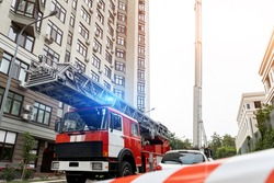 Many fire engine trucks with ladder and safety equipment at accident in highrise tower residential apartment or office building in city center. Emergency rescue at disaster