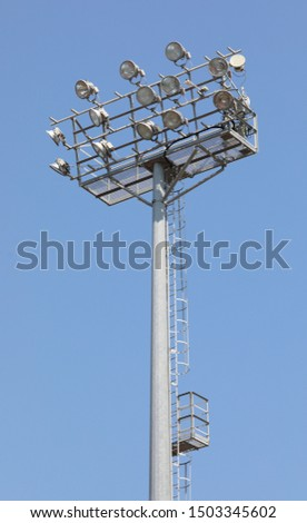 many floodlights in the pole at stadium without people and blue sky on background #1503345602