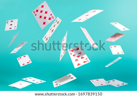 Photo of  many flying playing cards on a turquoise background