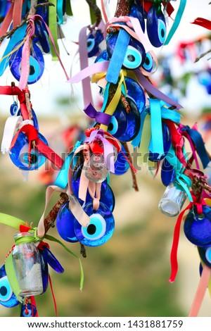 Many glass mascots - evil eye charms hang from a tree in Cappadocia, Anatolia, Turkey