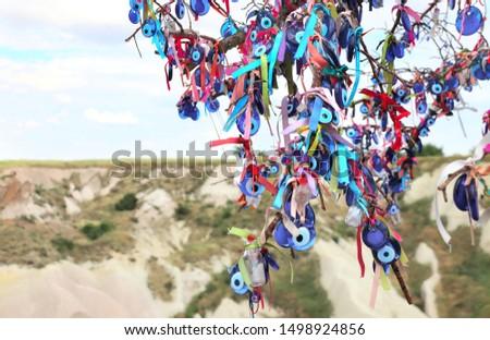 Many glass mascots - evil eye charms hang from a tree in Cappadocia, Pigeon valley, Anatolia, Turkey