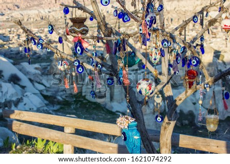 Many glass mascots - evil eye charms hang from a tree in Cappadocia, Pigeon valley, Turkey .