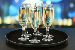 Many glasses of champagne on the tray on table, on bright background