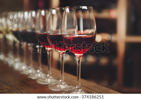 Many glasses of different wine in a row on bar counter #374186251