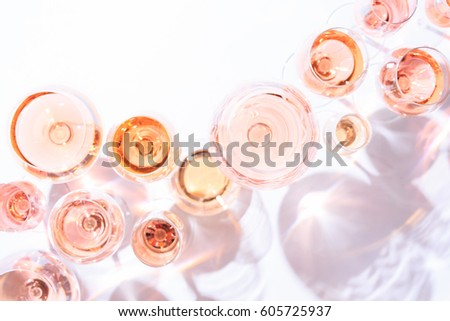 Many glasses of rose wine at wine tasting. Concept of rose wine and variety. White background. Top view, flat lay design. Direct sunlight. Toned image. Living Coral Pantone color of the year 2019