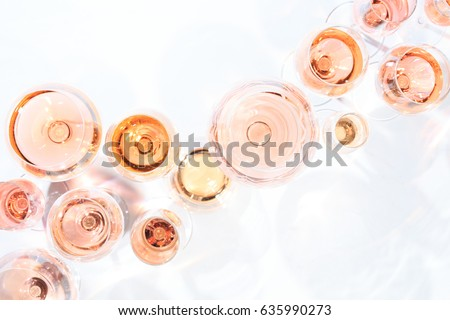 Many glasses of rose wine at wine tasting. Concept of rose wine and variety. White background. Top view, flat lay design. Horizontal. Living Coral Pantone color of the year 2019 shade
