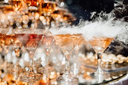 Many Glassware with Smoking Cocktail Beverage. Elegance Rich Buffet Decoration for Jubilee of Birthday or Wedding. Delicious Drink with Special Effect for Guests. Catering and Restaurant Service