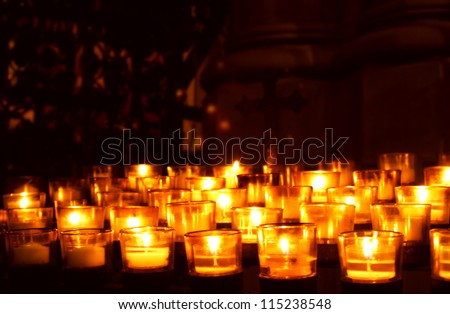 Many glowing votive prayer candles in church