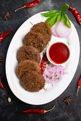 Many Goan beef or chicken cutlet, tomato sauce Goa South India. hot and spicy tea time snack on white plate, dark black background. fried meat of veal, mutton, fish. Top view Indian snack non veg food