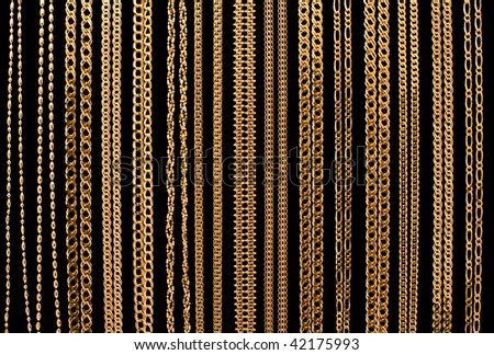 many gold chain necklaces over black background