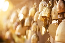 Many golden buddhist bells with wishes in sunlight