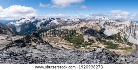 Many Great Peaks of the Glacier Peak Wilderness stretch ascross the horizon in this large panoramic vista. Cascade Mountains, Washington Foto stock ©