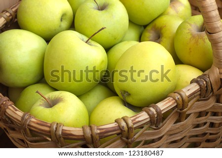 Many green and yellow apples in brown wicker basket vertical view closeup