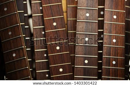 Many guitar necks aligned. Rosewood and ebony finger board electric guitar necks.  #1403301422