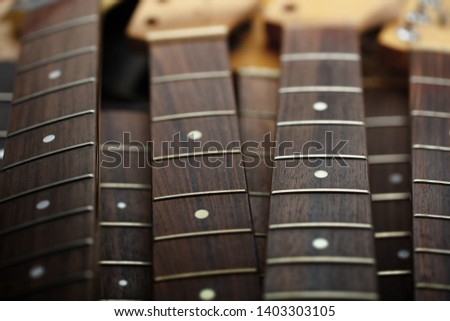 Many guitar necks aligned. Rosewood and ebony finger board electric guitar necks made from maple. #1403303105