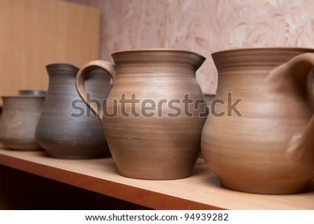 Many handmade old clay pots on the shelf.