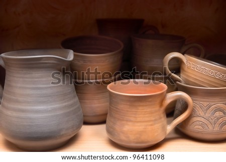 Many handmade old clay pots on the shelf.