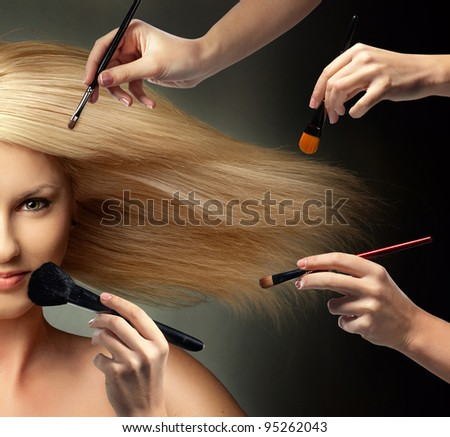 many hands applying make up on a woman face
