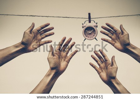 Many hands competing against one another to reach a clock hung on a rope - Time waits for no man