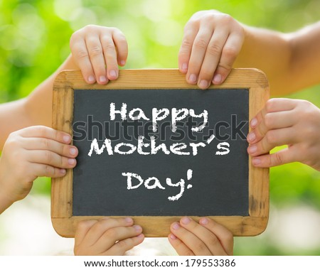 Many hands holding blackboard against spring green background. Mother\'s day greeting concept