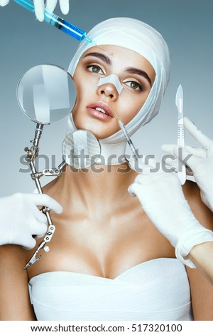 Many hands holding medical instruments near face patient. Nurses holding magnifying glass, scalpel, syringe near her face. Plastic Surgery concept
