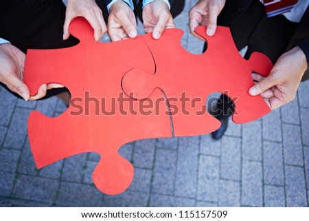 Many hands holding two red jigsaw puzzle pieces